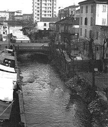 Milano Ticinese Darsena anni '50. Il ponte nella foto congiungeva Corso Cristoforo Colombo con Corso Genova e il canale sottostante era l'Olona che confluiva nella Darsena (una diramazione che da Piazza de Angeli alleggeriva il deflusso del colmatore dal ramo che confluiva verso la Torre delle Milizie sottopassando il Naviglio verso la Via Malaga in zona Barona. Pochi anni dopo lo scatto di questa foto il canale venne tombato ampliando la Piazza Cantore. A causa dell'inquinamento industriale e anche domestico del colmatore Olona (dalla Via Malaga, Lambro Meridionale), nel 1980 venne interdetta la confluenza delle acque (ormai tombate) verso la Darsena e verso i Navigli Pavese e Grande (contaminati da agenti chimici e biologici negli anni '60, '70 sino al 1980. Fonte Wikizero https://www.wikizero.com/it/File:Olona_che_entra_in_Darsena.jpg