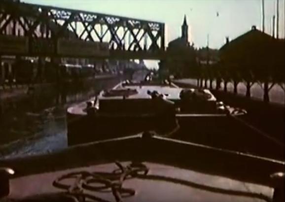 San Cirstoforo 1962. Barconi lungo il Naviglio Grande-Via Lodovico il Moro ponte ferroviario 1962. Sulla sinistra è visibile il tram Milano Corsico. Fotogramma acquisito da un cortometraggio super8-16 mm (con audio) edito da Carlo Borroni.