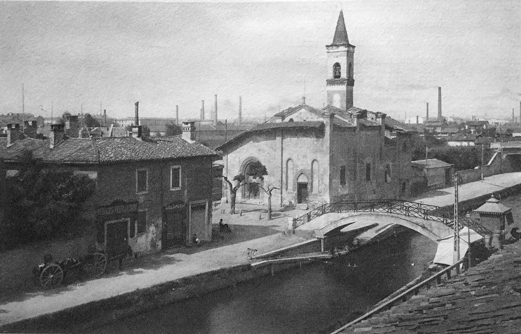Chiesa San Cristoforo fotografata dalla Via Lodovico il Moro (fine anni '20). Sullo sfondo le ciminiere ANSALDO del quartiere Tortona-Solari (hiveminer.com)