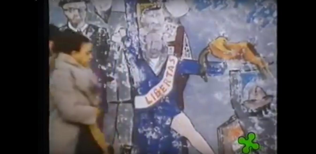 """Milano Barona 1982/83. Fotogramma dal film di Ermanno Olmi """"Milano 1983"""", Murales in Piazza Miani. Questo film, già da allora, contestava gli aspetti disumani di un certo """"sistema Milano"""", che dopo Tangentopoli '92, divenne ulteriormente dominante sconfinando negli affarismi politico imprenditoriali, nelle speculazioni edilizie, nello sfruttamento del lavoro precario, nel sistema tangenti degli appalti e in una """"vetrina"""" di falso benessere e bengodi che nascondeva miserie e arretratezze culturali che ebbero l'apice nel ventennio Berlusconista i cui effetti sono tutt'oggi ben presenti e radicati."""