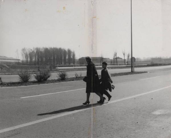 ... rifacendosi alle immagini sottostanti, dedicate al quartiere Sant'Ambrogio primo, negli anni '60 ed al suo isolamento dal resto del quartiere Barona e della città di Milano, una interessante immagine (seconda metà anni '60) scattata in Via del Mare, parallela alla Via San Paolino, poco a sud della Cascina Monterobbio. Una mamma e suo figlio attraversano, a piedi, la Via del Mare per raggiungere Piazza Maggi e, probabilmente, la filovia 95 e l'autobus che all'epoca serviva l'antistante quartiere Torretta, onde raggiungere il resto di Milano (il capolinea del tram 12 di Piazza Miani, da quel settore del plesso di edilizia popolare, distava circa 1 km...). A breve verranno sinteticamente elencate le concause di scarsi investimenti ATM relativi ai servizi e collegamenti tramviari e di autobus delle zone periferiche a cavallo degli anni '50 e '70... Tra le cause principali i costi per le realizzazioni delle linee MM 1 e MM2 (che fagocitavano le restanti risorse...), una preferenza del Comune verso le zone periferiche a Nord-Nord Est della città (quelle piu' vicine ai poli industriali ed alla Brianza...) e le politiche Nazionali della ex Democrazia Cristiana... (a Milano le giunte, sino a metà anni '70 erano socialdemocratiche... ma controllate dalla DC romana...). Le politiche DC erano concentrate a favorire i ladrocini per la Cassa del Mezzogiorno e di Roma Capitale... sono storie vecchie ma ancora attualissime... Fonte fotografica: Lombaria Beni Culturali.