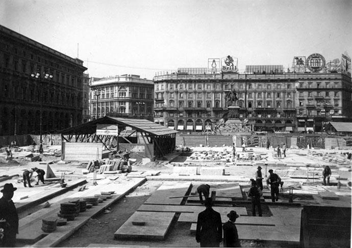 Piazza Duoo 1929. Rifacimento della pavimentazione su progetto del Portaluppi. Si nota una prevalenza di insegne pubblicitarie, per paradosso, sul palazzo attiguo a Palazzo Carminati.