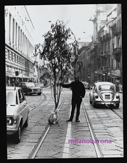 """Milano 1973, Via A. Manzoni-Montenapoleone. Posa provocatoria dello scultore austriaco Friedensreich Hundertwasser (artista con ideali ecologisti). In una Milano (ieri come oggi) povera di verde, cementificata in ogni dove, città piccola ma ricca di concentrazioni di cemento da assomigliare a Palermo, Friedensreich Hundertwasser volle farsi fotografare in una via centrale e """"prestigiosa"""", che pur se inserita in un contesto urbano storico e secolare... rivela errori urbanistici """"secolari"""" a partire dalla scarsità di verde pubblico e urbano fruibile sia nel centro storico come nelle periferie."""