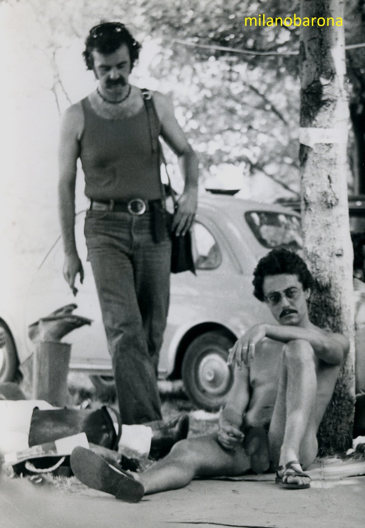 """Milano 1976. Parco Lambro, Festival del Proletariato Giovanile. Borselli maschili a tracolla in pelle e occhiali Ray Ban accompagnavano stili di vita e accessori della vita (più o meno quotidiana) degli anni '70. Per la """"piccolo borghesia"""" anche l'autoradio estraiebile """"Autovox"""" (infilata nei borselli o trasportata a mano) rappresentava lo stile di vita piccolo borghese di quel periodo. Il Festival del Proletariato, organizzato dai vertici milanesi e lombardi del PCI generava malcontento e polemiche tra i militanti più radicali per i contenuti commerciali e """"consumistici"""" impresso dalla Classe Dirigiente di un Partito Parlamentare che non seppe rappresentare e gestire il disagio giovanile."""