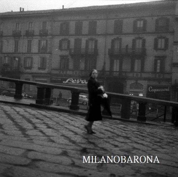 Milano 1955 , Darsena a ridosso del Ponte dello Scodellino. Alzaia Naviglio Grande. Da notarsi la pavimentazione a lastricato sostituita dall'asfalto negli anni '60. (autore Ernesto Treccani, fonte Lombardia beni culturali)