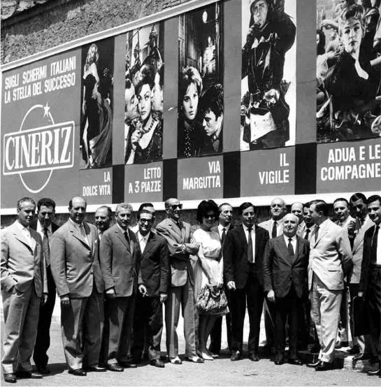Anni '60 del 900. Angelo Rizzoli con alcuni collaboratori dell'industria cinematografica CINERIZ (località non precisata e non identificabile). In evidenza alcune locandine delle principali produzioni di quel periodo (fonte biografia A. Rizzoli)