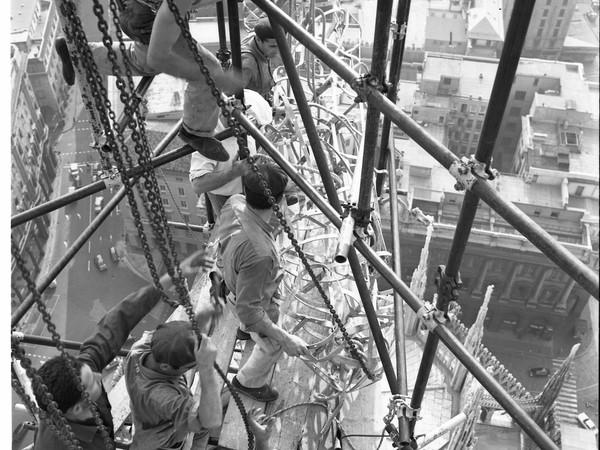 Duomo di Milano, Luglio 1967, sommità sottostante alla Madonnina. Restauratori (della Madonnina) acrobaticamente sostenuti dalle impalcature elevate ad una quota prossima ai 108 metri. (immagine dell'Archivio della Veneranda Fabbrica). Fonte web dell'immaine : arte.it