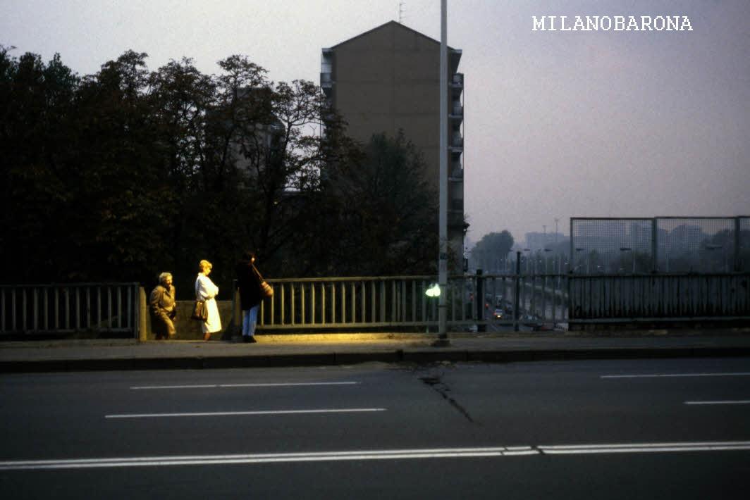 Milano 1990, Barona. Cavalcavia Don Lorenzo Milani (autore Cesare Colombo). Fonte web Lombardia beni culturali. L'autore della foto ha cercato di esaltare un effetto di illuminazione diretta prodotta dal fascio di luce di un lampione su un gruppeto di persone in attesa dell'autobus 95 (oggi sostituita dalla 98).
