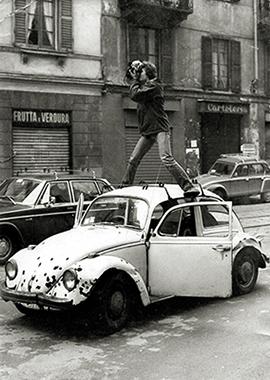 """Corso Italia 1978. Curiosa immagine di un fotoreporter posizionato sopra il tetto di una Wolkswagen """"Maggiolino"""" . (fonte immagine web andrearovatti.it)"""