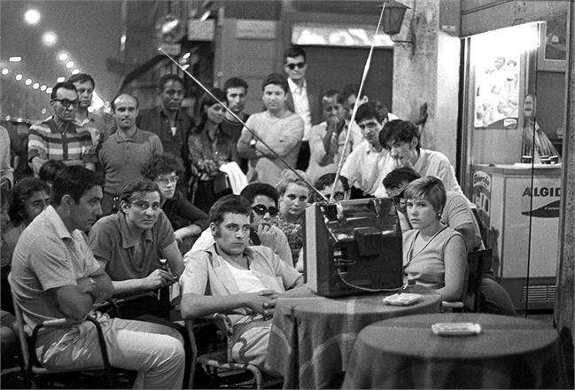 """Milano 20 Luglio 1969. Prime ore del mattino durante la diretta notturna (seguita in un bar milanese con un televisore allestito tra i tavolini posti sul marciapiede) della Missione Apollo 11 che ufficialmente consacrava il primo sbarco dell'uomo sul satellite naturale terrestre. L'ultima missione avvenne nel 1972 (Apollo 17). Verso il 1976, negli USA, vennero stampati e venduti libri (co-redatti da ex ingegneri della Aerojet Rocketdyne, la principale ditta appaltatrice delle missioni lunari NASA) dove si mise in discussione la veridicità dell'evento. La diatriba è in corso ancora oggi e non mancherebbe alcuni validi argomenti a favore dei cosiddetti """"complottisti lunari"""". A distanza di mezzo secolo nessuna delle due fazioni (NASA e complottisti) è in grado di dimostrare, nell'ordine, che sulla Luna gli USA ci andarono realmente o, viceversa, non ci andarono mai ... con un eventi etichettato come la più grande fiction mediatica e televisiva su scala planetaria. Ci andarono o no ? Un segreto che tutt'oggi non ha risposte certe. Fonte fotografica VOGUE"""