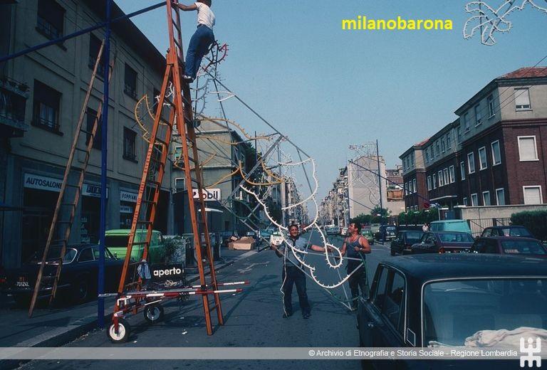 """Milano 1982. Lorenteggio/Giambellino. Via Vespri Siciliani, allestimento stradale """"Festa del Giglio"""" (Lombardia beni culturali)"""