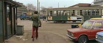 """Milano 1974, Porta Genova-Ticinese. Piazzale Stazione di Porta Genova e capolinea tram 9 con vettura """"28 o 1928"""" ferma al capolinea medesimo. Fotogramma dal film """"Milano odia la polizia non può sparare"""" di Umberto Lenzi, genere """"moir"""" ma più prossimo al """"poliziottesco"""" tipici del periodo. La figura che appare alle spalle è Tomas Milian (Giuliano Sacchi 1933 2017). Vettura """"Peter Witt"""" con asta di captazione elettrica, non ancora implementata di doppia alimentazione a semipantografo... in corso in quegli anni. Ovviamente livrea nel """"verde ministeriale"""" bicolore adottata tra la fine degli anni '20 sino agli anni '70. Fonte fotografica IMCDb.org"""