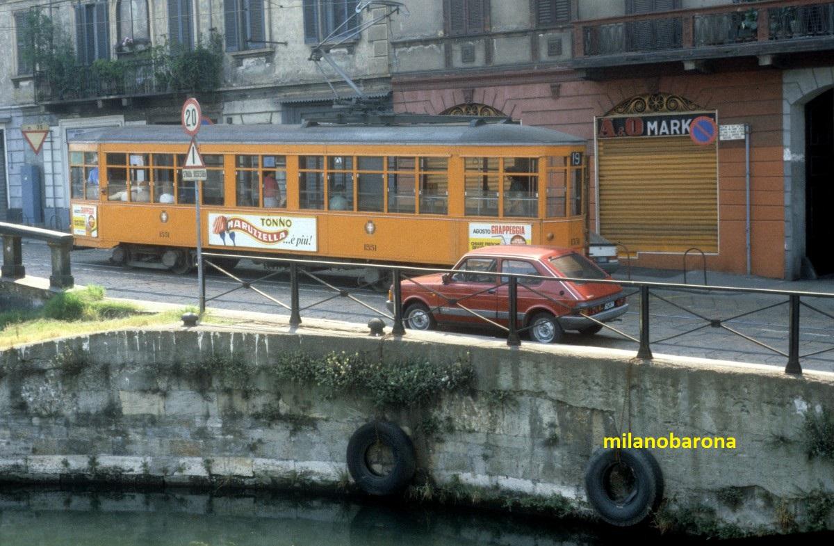 Milano 1984, Ticinese-Darsena. Ripa di Porta Ticinese verso Viale Gorizia a ridosso del Ponte dello Scodellino. Ultime settiname di transito del tram 19 (Roserio-Negrelli) prima della sospensione di tale tratta tramviaria (siamo nell'Agosto 1984) e la definitiva dismissione (il 19 verrà deviato lungo la Via Valenza, verso la stazione FS di Porta Genova). Otto mesi circa venne inaugurata la tratta Cadorna-Porta Genova della linea M2 della metropolitana (questo comportò la deviazione della linea tramviaria 19 verso Porta Genova con l'abbandono della tratta Ripa Ticinese, Gorizia, XXIV Maggio, Corso di P.ta Ticinese).