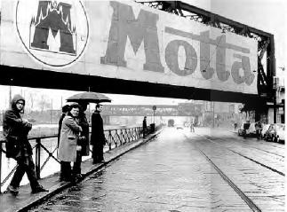 """Barona primi anni '70. Ponte ferroviario di San Cristoforo e Via Lodovico il Moro verso Ripa di Porta Ticinese. In evidenza (anche se in secondo piano) il vecchio ponte veicolare delle Milizie, demolito e completamente rifatto nella seconda metà degli anni '70. La gigantografia pubblicitaria Motta (insieme alla pubblicità del Supecortemaggiore ENI-SNAM-AGIP installata sul lato opposto del ponte, costituivano una forma di pubblicità permamente che sopravvisse dagli anni '60 sino a buona parte degli anni '70 . (fonte web """"Milano periferia"""", libro omonimo, pubblicato in formato """"slide-motion"""" nel sito laboratorioimmagine.it)"""