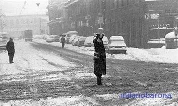 """Milano 1985, Porta Genova. Storica nevicata del Gennaio 1985 (nell'immagine l'evento è solo all'inizio, presumibilmente il 13 Gennaio 1985, meno di 16 ore dall'inizio della nevicata che incomincio' il tardo pomeriggio del 12 Gennaio per esaurirsi il 16 Gennaio dopo aver messo """"in ginocchio"""" l'intera città di Milano e parte della Lombardia sud occidentale (i massimi di neve si raggiunsero nelle province di Milano, Pavia, Lodi, Cremona, mentre il fenomeno fu più limitato , ma comunque intenso, nelle province di Bergano e Brescia... mentre nelle province di Como e Sondrio e nelle aree alpine e prealpine la neve cadde con minore intensità). Da notarsi, sul lato dx dell'immagine, una campana arancione dell'allora raccolta differenziata del vetro. (fonte milano,repubblica.it)."""