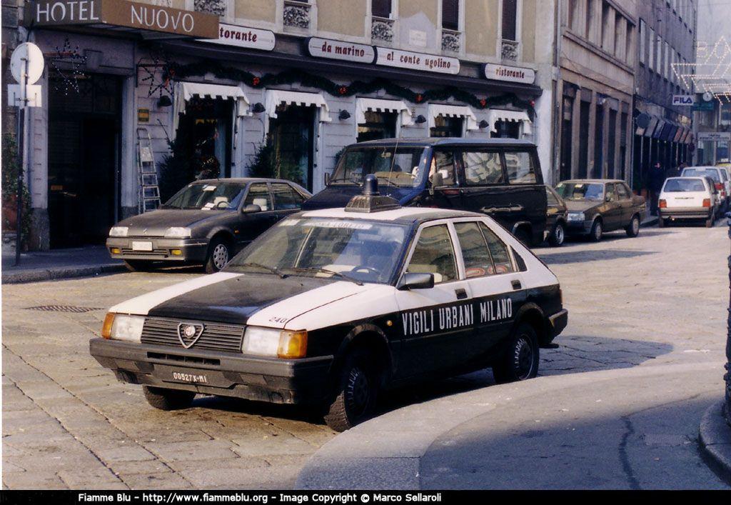 """Milano Via e Piazza Cesare Beccaria, 1984 circa. Pattuglia Vigili Urbani posteggiata a ridosso del Comando di Piazza Beccaria. L'Alfa Romeo ARNA è storicamente nota per essere stata un modello d'automobile dove vennero commessi degli errori progettuali (di stile, ovviamente) nei quali il design del modello venne affidato alla giapponese NISSAN e l'attrezzatura motoristica all'ALFASUD. Ne nacque una vettura, anni '80, piu' allineata agli stili e gusti nipponici rispetto al """"design"""" italiano, notoriamente """"aggressivo"""" e sportivo delle vetture ALFA ROMEO. Un errore simile venne compiuto, dalla FIAT, sempre nello stesso periodo per la nota """"DUNA"""" (in questo caso il designe era pero' italico di Giorgetto Giugiaro)."""