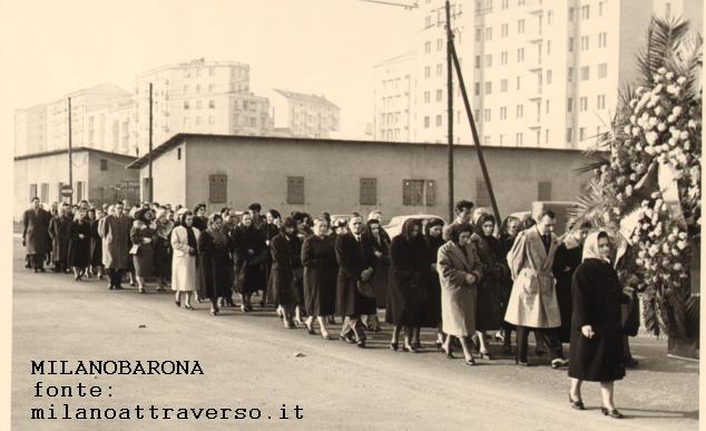 Milano 1959, Bande Nere-Lorenteggio. Corteo funebre in Viale Caterina da Forlì. In evidenza le case minime edificate nello spartitraffico intermedio del viale. (fonte:milanoattraverso)