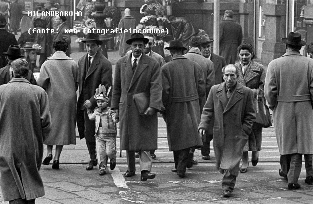 """Piazza Cordusio 1955. Autore Cesare Colombo, apparentemente immagine non correlabile a fotogrrammi da film. Un bambino in costume da indiano accompagnato da due uomini dall'aspetto singolare (borse portadocumenti in stile """"faccendieri"""" (o giù di li...). Non è dato sapere se l'immagne sia stata sfruttata dai monopolisti Milano Sparita Skyscrapercity e Facebbook. (fonte web_fotografieincomune.comune.milano)"""