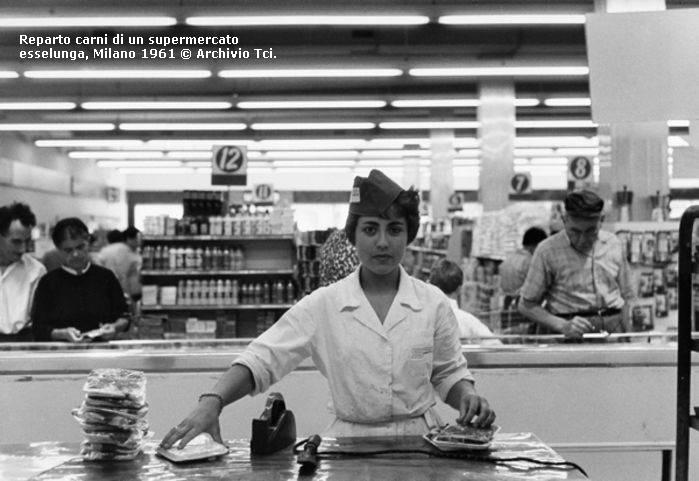 Milano 1961. Addetta alla etichettatura confezioni di carne in un negozio Supermaerket. Località di Milano non precisata. Fonte immagine web TCI, Touring Club Italano