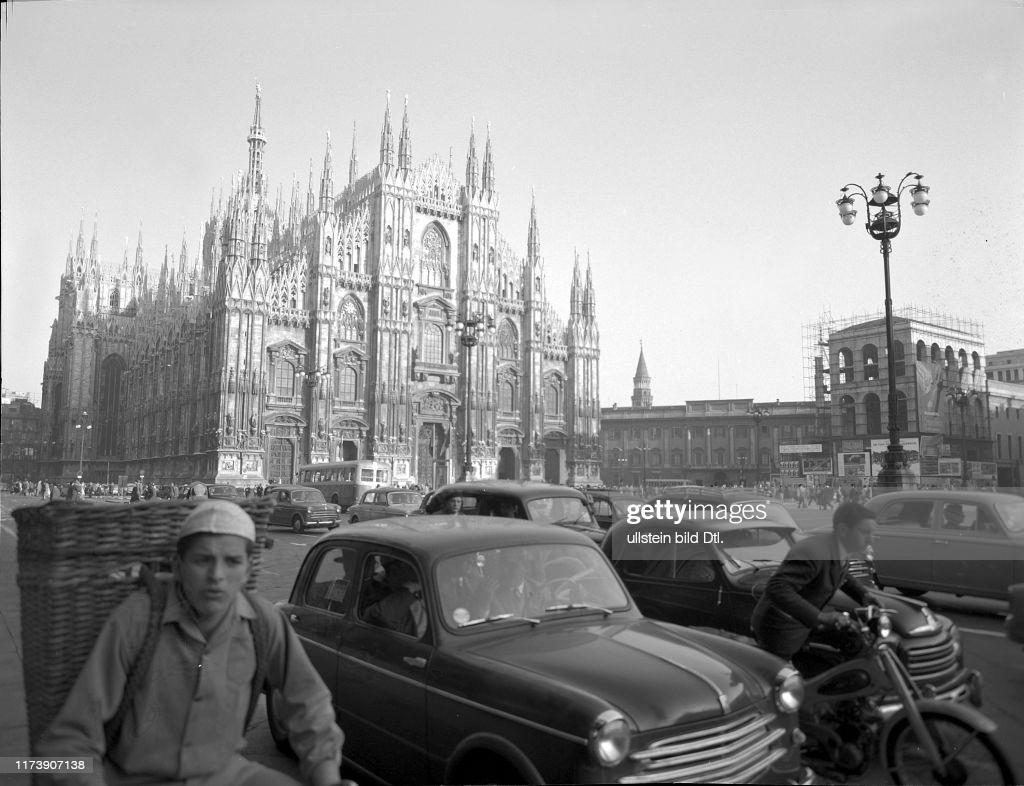 """Piazza Duomo 1956. Malgrado la ancora scarsa motorizzazione del periodo, una Piazza Duomo ed un Corso Vittorio Emanuele (ancora attraversato dai tram) invaso da automobili. Erano i tempi della circolazione stradale """"radiale"""" assecondata nell'ex Piano Regolatore PRG 1953 che voleva le circonvallazioni come anello di traffilico locale, da quartiere a quartiere, e le arterie che solcavano il centro storico come passaggio rapido tra gli estremi opposti della città, verso destinazioni autostradali... progetto e filosofia urbanistico-metropolitana abbandonato nel 1958, o quantomento """"congelato"""" per non essere mai più ripreso nei decenni successivi. Autore immagine: Milou Steiner."""