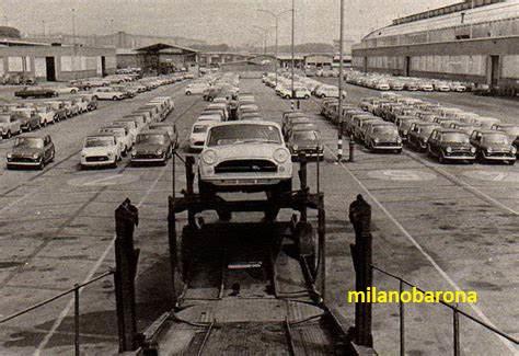 """Milano Lambrate fine anni '60. Stabilimenti Innocenti e una Mini Mini Minor in caricamento sul camion """"bisarca"""". Datazione immagine assente, il modello di auto parcheggiate nel piazzale della Innocenti è simile al modello Mini Mini Minor MK3 838/2 prodotto intorno al 1970 https://www.automobile.it/bergamo-innocenti-mini-mini-minor-mk3-838-2/133730901"""