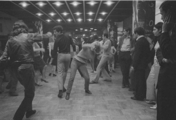 """Piper (Aprile 1966). Pista da ballo nella serata di inaugurazione del """"Piper"""" di Milano (attuale """"Old Fashion""""), discoteca che si rifaceva, a tutti gli effetti al Piper Club di Roma, fondato da Alberigo Crocetta e Giancarlo Bornigia nel Febbraio 1965 a Roma (ufficialmente la prima discoteca italiana che si differenziasse dalle """"balere"""" sino all'epoca esistenti anche come ritrovo giovanile). Il Piper Milano, similmente a quello di Roma, ospitò personaggi come Patty Pravo, Lucio Dalla e altri grandi nomi della musica Italiana vivacizzando le notti Milanesi sino ad allora contraddistinte dall'assenza di vita-notturna. Nel Giugno del 1968 , in tale locale, si tenne un concerto di Jimi Hendrix. Rispetto al Piper romano la vita di questo locale ebbe vita breve alternando cambi di gestione fallimentare sino alla ristrutturazione del 1970 con il nome attualmente esistente di Old Fashion. Autore immagine Carla Cerati (fonte web immagine Lombardia Beni Culturali)."""