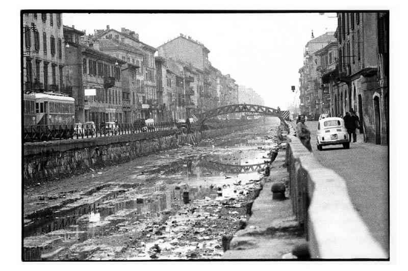 Ripa di Porta Tcinese, Naviglio Grande (in secca), anni '60 (anteriore al 1966 per via della elettromotrice tranviaria in transito della linea Milano Corsico, soppressa dal Marzo 1966). Autore Carla Cerati (fonte web miafair)