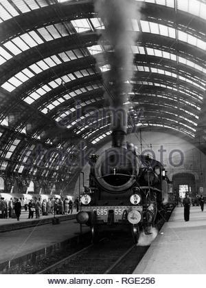 Stazione Centrale 1955. Suggestiva emissione di fumo nero da una locomotiva a vapore. effetto di un eccessivo afflusso di comburente (aria) nella caldaia a carbone. La combustione troppo rapida trascina con se particolato di carbone espluso dal camino, con l'effetto di uno spreco di carburante a locomotiva ferma... forse una manovra per spingere a regime (mandare a pressione) la caldaia in tempi rapidi.